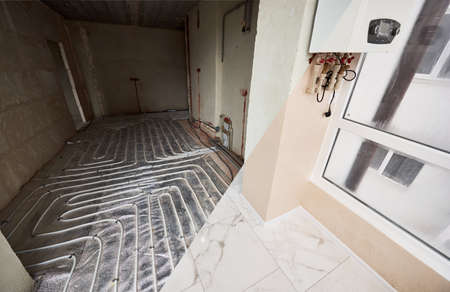 View from glazed loggia to new spacious room with warm floor. Electric floor heating. Pipe system of heating under white tiles, hidden gas boiler. Concept of home renovation and restoration. 版權商用圖片