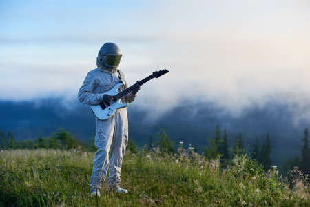 Spaceman in white space suit and helmet holding white guitar standing on beautiful green mountain meadow in the morning, fog is rising up from the valley on background. Concept of music, astronautics.