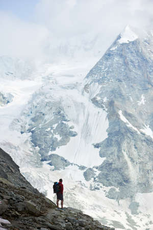 Vertical snapshot of incredibly beautiful mountain in Swiss Alps. Man tourist standing on a slope enjoying a cold quiete scenery. Concept of freedom, mountain hiking, tourism and alpinism