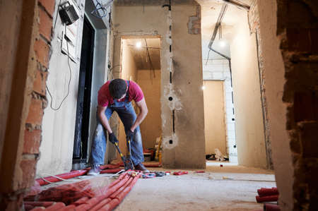 Young plumber wearing blue overalls and gloves installing underfloor heating system in new apartment. Man working with pump plier, flooring red pipes in unfinished building. Concept of home renovation