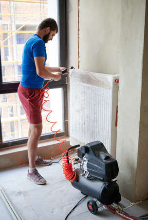 Side view of plumber filling pipes with pressurized air to inspect for leaks in new installation, using air compressor while checking gas tightness of heating system. Concept of gas tightness testing.