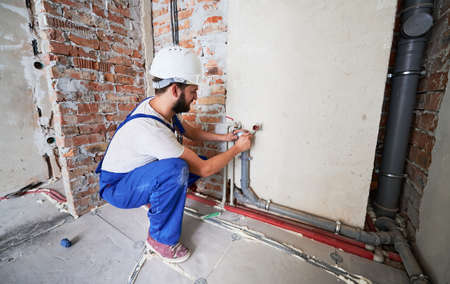 Bearded young man in work overalls installing heating pipes in apartment. Male worker in safety helmet doing maintenance jobs for water and heating systems. Concept of plumbing and home renovation.
