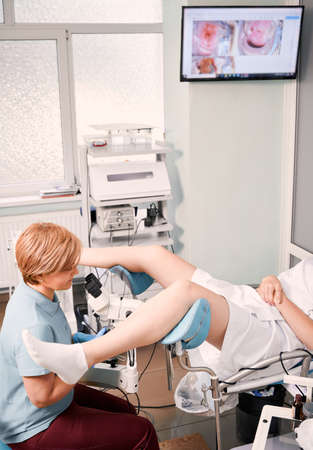 Woman sitting in gynecological chair while doctor performing gynecologic examination. Female gynecologist in blue shirt examining patient with colposcope. Concept of female health and gynecology.