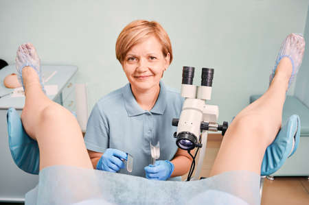 Female doctor in sterile gloves using colposcope and gynecological retractors while examining woman in clinic. Gynecologist looking at camera and smiling while patient sitting in gynecological chair.