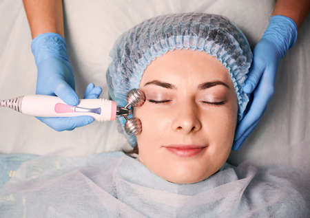 Close up of cosmetologist hands using anti-aging microcurrent face roller while massaging female client face. Young woman in disposable shower hat having galvanic massage in beauty salon. Stock fotó