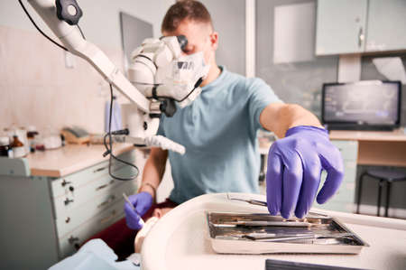 Close up of male dentist hand in sterile glove holding metal dental explorer while checking patient teeth. Stomatologist taking instrument while sitting near microscope. Concept of dentistry.