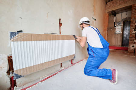 Man in work overalls using wrench while installing heating radiator in room. Young plumber installing heating system in apartment. Concept of radiator installation, plumbing works and home renovation.