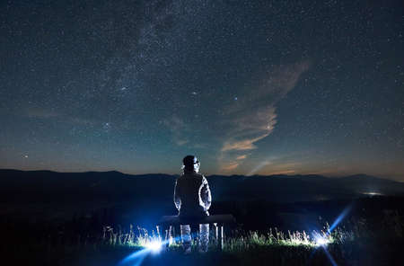 Back view of spaceman sitting on bench looking at majestic starry sky. Cosmonaut in space suit enjoying the view of magical blue night sky with stars. Concept of space travel, galaxy and cosmonautics. 写真素材