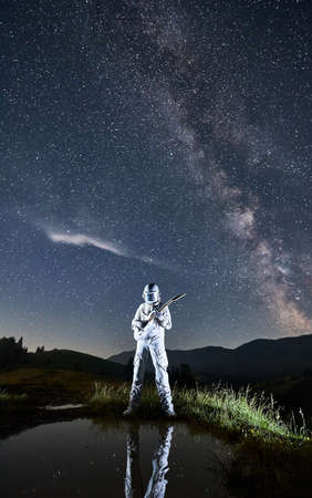 Astronaut guitarist wearing space suit standing at the lake playing guitar at night, legs reflected in the water, Milky way in starry sky on background. Concept of music, cosmonautics and galaxy.