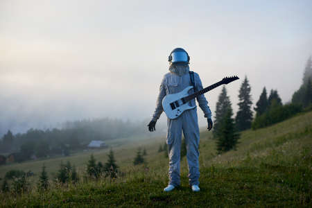 Cosmanaut wearing white space suit and helmet holding white guitar standing on beautiful green mountain meadow in the morning, foggy spruce forest on background. Concept of music, astronautics, nature