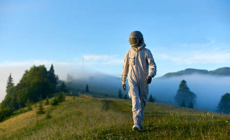 Spaceman wearing white space suit and helmet walking alone sunny green mountain glade in the morning, foggy hills and blue sky on background. Concept of astronautics, Earth exploration and nature