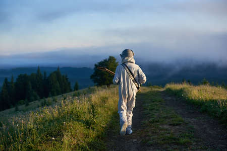 Back view of space traveler walking on mountain road and playing melody on guitar. Cosmonaut guitarist in white space suit strolling down grassy trail. Concept of music, astronautics and nature.