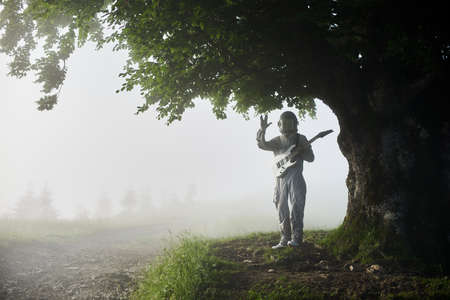 Talented spaceman wearing white space suit and helmet holding white guitar is standing under a huge beautiful tree in foggy summer morning, concept of exploring Earth 写真素材