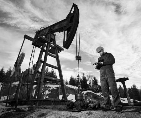 Male worker using notebook controlling work of petroleum pump jack. Operator standing near oil pumping unit. Concept of petroleum industry and oil extraction. Black and white image