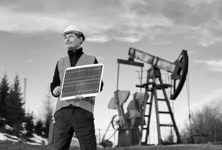 Businessman holding portable solar panel. Worker standing on territory of oil field with pump jack on background. Concept of petroleum industry and alternative energy sources. Black and white image