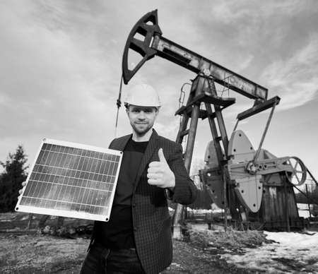 Businessman holding mini solar module and showing thumb up, standing in oil field next to oil rig. Concept of petroleum industry, alternative energy sources. Black and white image