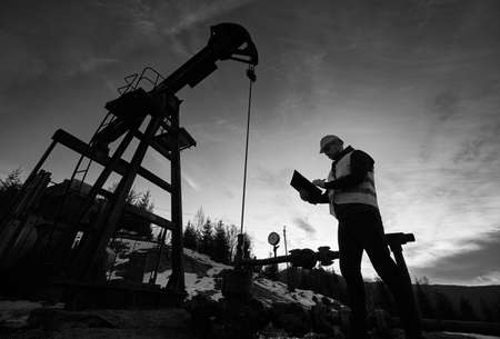 Low angle of petroleum engineer looking at oil pump rocker-machine and writing on clipboard. Silhouette of oil worker checking work of balanced beam petroleum pump jack. Black and white image 写真素材