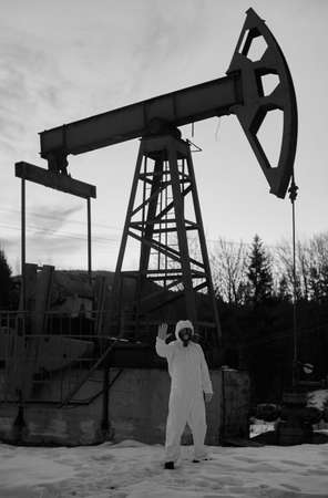 Scientist in gas mask standing on territory of oil field with oil pump rocker-machine on background. Researcher showing stop sign in front of oil pump jack. Concept of ecology. Black and white image