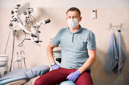 Portrait of man dentist in sterile gloves and medical mask looking at camera. Male stomatologist sitting near dental microscope. Concept of dentistry and stomatology.