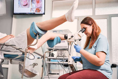 Gynecologist using colposcope while examining woman in gynecological clinic. Female patient laying in gynecological chair. Concept of gynecology, medical examination and female health. 写真素材