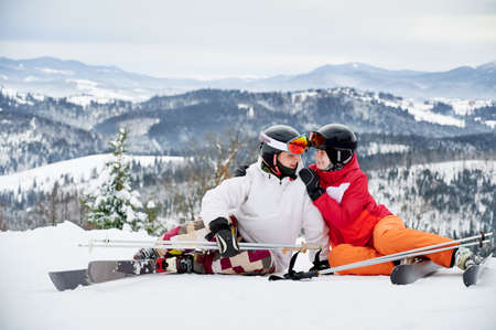 Charming young woman looking at man and smiling while wrapping arm around his shoulder. Joyful boyfriend and girlfriend sitting on snow-covered hill in mountains. Concept of skiing and relationships.