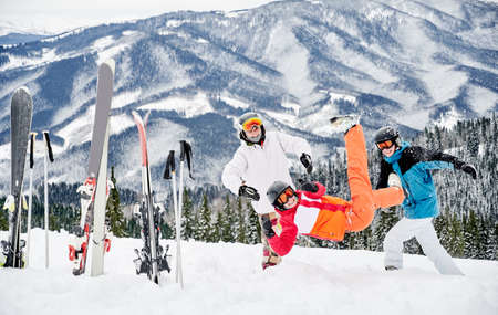 Group of friends in vivid winter sports suits having fun in snow in the mountains. Ski poles and skis stuck in snow, cheerful people are playing snow against beautiful mountains background. 写真素材