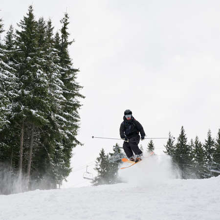 Full length of male skier skiing on fresh powder snow with coniferous trees and sky on background. Man freerider making jump while sliding down snow-covered slopes. Concept of winter sport activities.