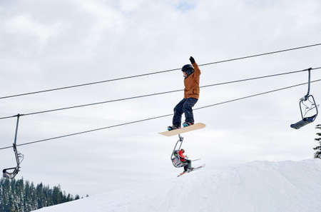 Boy sowboarder doing tricks in the mountains ski resort, flying up high with snowboard against chairlift and cloudy sky. Low angle view. Concept of winter kinds of sport, extreme sport.