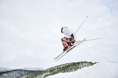Horizontal snapshot of spectacular freeriding fly at the steep slopes by male skier. Cool ski jump from hill against cloudy sky on background. Low angle view, copy space. Extreme sport concept