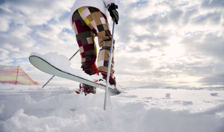 Close-up, low angle view snapshot of skiers legs. Man skiing, making a jump up on white snowy surface against beautiful cloudy sky. Copy space. Concept of winter sport activities. 写真素材