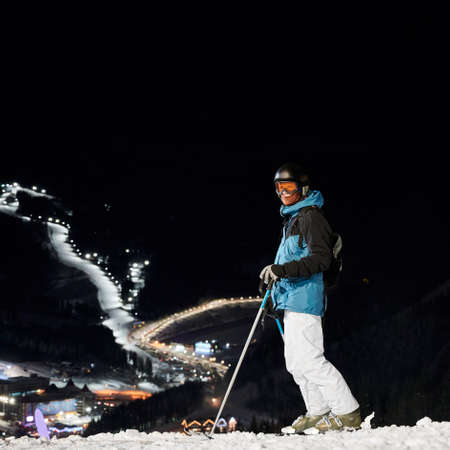 Full length of man skier in winter ski jacket and helmet holding ski poles and looking at camera. Young man in ski goggles standing on snow-covered slope with beautiful night city on background. 写真素材