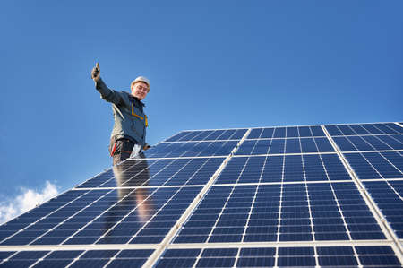 Male worker giving thumbs up and smiling while mounting blue photovoltaic solar panel under beautiful cloudy sky. Concept of alternative energy sources and innovations.
