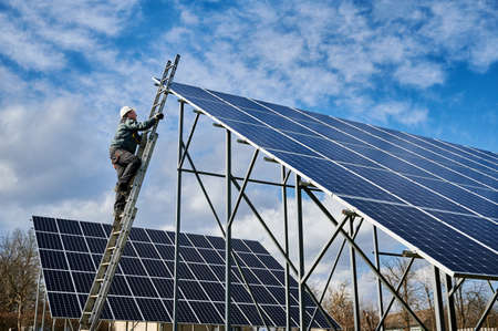 Man electrician in safety helmet climbing the ladder to get to the top of photovoltaic solar module. Technician mounting solar panels. Concept of alternative energy sources and innovations
