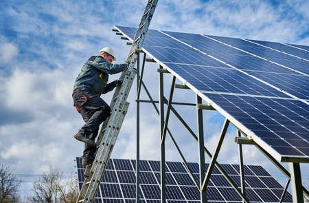 Technician getting down the ladder after installing photovoltaic solar panels on a sunny day. Renewable energy resource. Concept of alternative energy and power sustainable resources. Stok Fotoğraf - 161868639