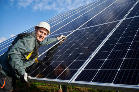 Joyful man electrician in safety helmet repairing photovoltaic solar module. Male worker looking at camera and smiling while maintaining solar photovoltaic panel system. Concept of alternative energy Stok Fotoğraf