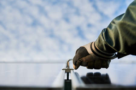 Close-up horizontal snapshot of installers hand in working glove holding hex key, fastening metal carcass to maintain solar batteries. Low angle view. Sky on background. Copy space Stok Fotoğraf - 161868641