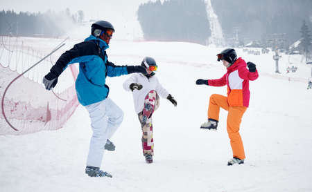 Group of friends wearing vivid ski suits warming up before skiing from piste in mountains in winter. Working out on snow, having fun together. Concept of active lifestyle, winter sport activities
