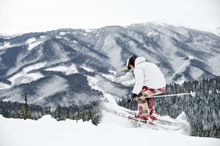 Winter kinds of sport concept. Skier wearing winter sports costume and ski equipment doing jump trick in winter season. Entertainments at ski resort in the mountains, rear view, copy space