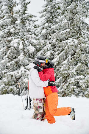 Young couple of tourists kissing in snow against mesmerizing snowy spruce forest on background. Vivid colorful suits on white snow. Concept of skiing and relationships. Stock fotó