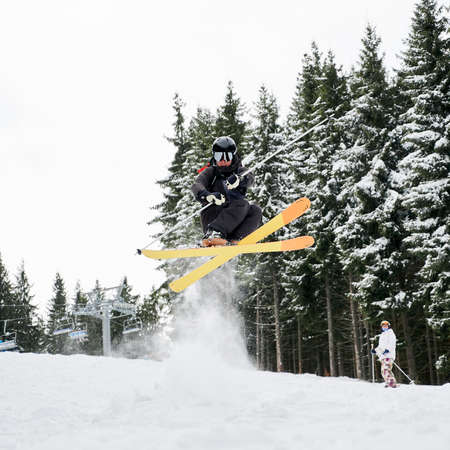 Male skier in ski suit and helmet skiing on fresh powder snow with snowy pine trees on background. Man freerider in ski goggles holding ski poles and making jump while sliding down snow-covered slopes Stok Fotoğraf - 161868647
