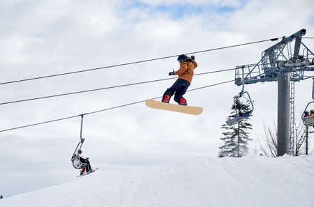 Snowboarder doing tricks in the mountains. Boy flying up high with snowboard against skilift and cloudy sky. Low angle view. Concept of winter kinds of sport, extreme sport at ski resort