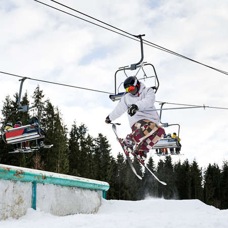 Jumping skier at jump in high at ski resort. Chairlift on background. Winter kinds of sport. Concept of extreme sport