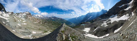 Panoramic scenery in sunny day with blue sky and clouds, beautiful mountains area with snow. Gorgeous mountain ridge with high rocky peaks, wonderland in Alps.