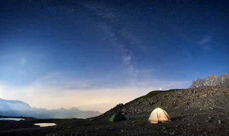 Magic scenery at night with blue sky and shining stars, beautiful mountains area with snow and lakes. Gorgeous mountain ridge with high rocky peaks, two colorful tourist tents. Panoramic view