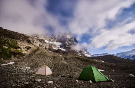 Panoramic view of night camping in night mountains. Scenery of tourist tents on rocky hill and mountain peak Matterhorn under beautiful misty sky with stars. Concept of travelling, hiking and camping.