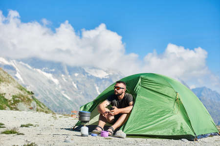 Male tourist in sunglasses sitting inside camp tent, enjoying scenery with mountains and blue sky on background in sunny warm summer day. Concept of travelling, touristm, alpinism, hiking, camping