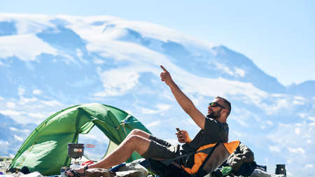 Male tourist sitting in chair near tent in empty rocky alpine mountains, using smartphone in sunny warm summer day and pointing with hand up. Concept of camping, travelling in Alps, nature, gadgets.
