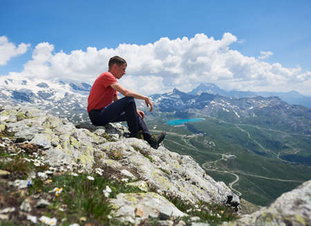 Side view of man hiker sitting on the edge of rocky hill under beautiful cloudy sky. Tourist enjoying the view of mountain valley with grassy hills and blue lake. Concept of travelling and hiking.