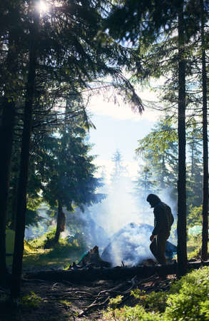 Guy in jacket and hood making fire and smoke flows up. Tent among fir trees under the rays of sun breaking through clouds on cold day. Camping in the forest