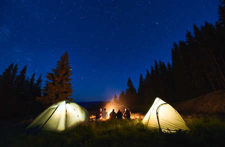 Rear view, tourists are sitting by brightly blazing bonfire between the tents against the backdrop of mountain valley and pine forest under blue night sky with bright stars. Outdoor activity concept Stok Fotoğraf